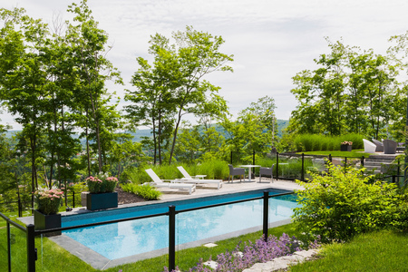 Sun loungers by outdoor swimming pool in residential backyard LANG_EVOIMAGES