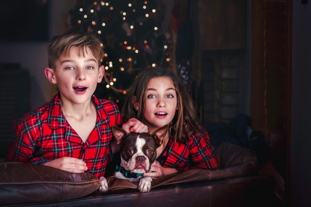 Siblings and pet dog leaning over sofa, excited