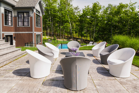 Chairs on backyard patio and rear view of contemporary luxurious bungalow style home