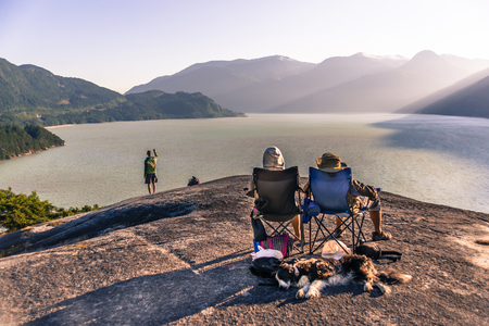 Friends relaxing in camping chairs on mountain ledge overlooking lake, Squamish, Canada LANG_EVOIMAGES