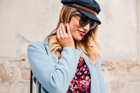 Portrait of woman wearing sunglasses and baker boy cap looking away LANG_EVOIMAGES