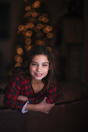 Girl leaning over sofa, smiling, Christmas tree in background LANG_EVOIMAGES