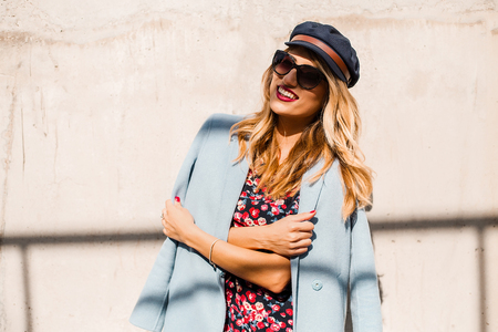 Stylish woman wearing sunglasses and cap in front of wall with arms folded LANG_EVOIMAGES