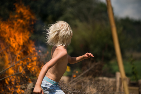 Blond haired boy running away from garden bonfire