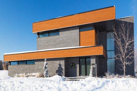 Modern grey brick and stained wood finish cube style house facade in winter