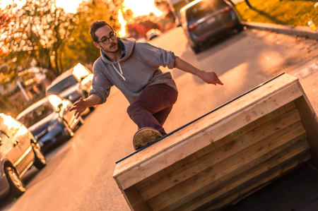 Young male skateboarder turning moving up ramp on suburban street at sunset LANG_EVOIMAGES