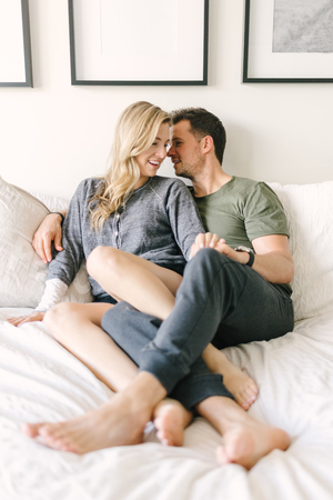 Couple relaxing on bed, legs entwined