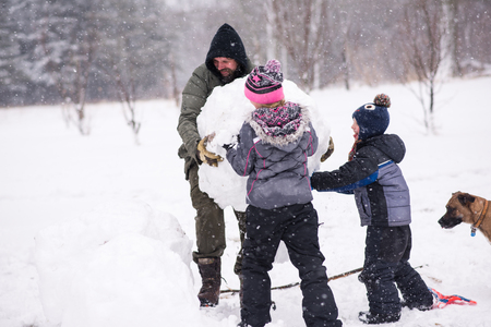 Father and children carrying large snowball