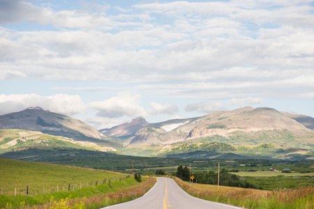 Landscape with rural road through mountain valley, Browning, Montana, USA