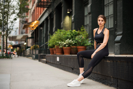 Portrait of woman wearing workout clothes sitting on wall looking at camera, New York, USA