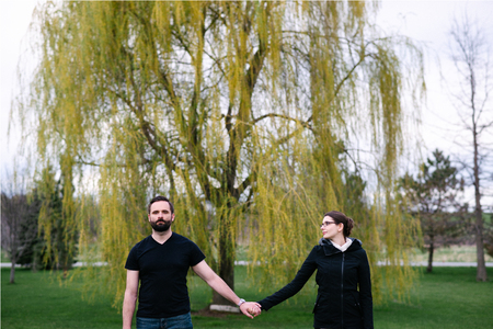 Couple in front of willow tree in park, Kingston, Canada