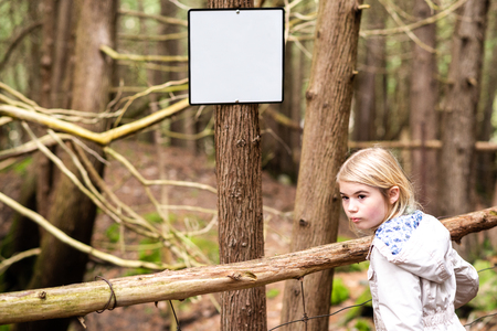 Girl looking back in forest next to blank notice board on tree trunk