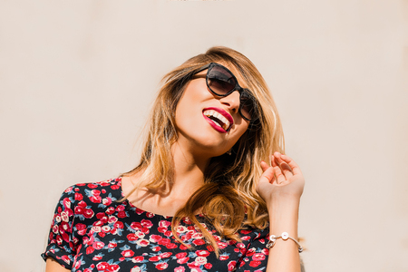 Blond, stylish mid adult woman wearing sunglasses in front of wall laughing