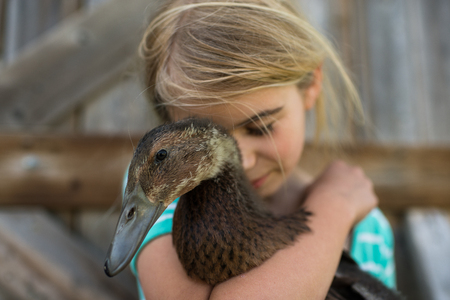 Girl with eyes closed hugging farm duck