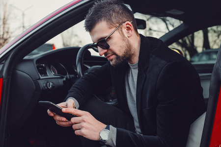 Bearded businessman using mobile phone in luxury car