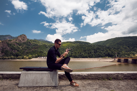 Man using mobile phone by beach, Draja, Vaslui, Romania