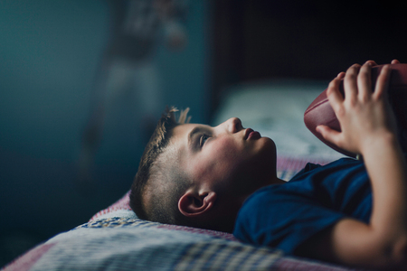 Boy on bed with american football LANG_EVOIMAGES