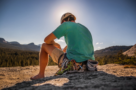 Young male climber sitting on top of rock formation, Tuolumne Meadows, upper part of the Yosemite National Park, California, USA LANG_EVOIMAGES
