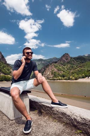 Man using mobile phone by beach, Draja, Vaslui, Romania