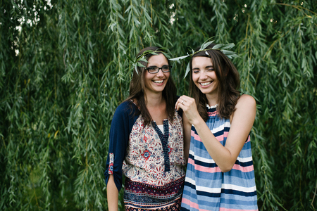 Twin sisters beside weeping willow branches