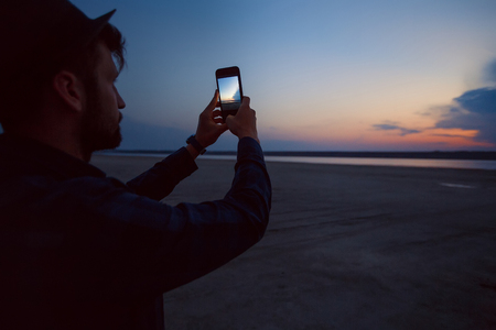 Man in hat taking photograph of sunset on beach, Odessa, Ukraine