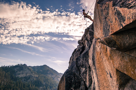 Young male rock climber on rock face, High Sierras, California, USA