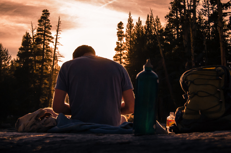 Young male hiker taking a break at sunset, Tuolumne Meadows, upper part of the Yosemite National Park, California, USA
