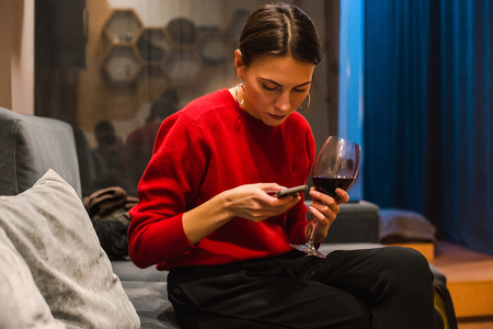 Woman texting on mobile phone while at party