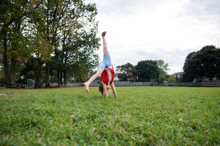 Girl doing cartwheel in park