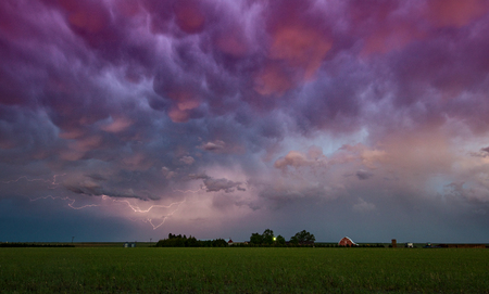 Lightning under storm cloud over farmhouse, Wray, Colorado, US LANG_EVOIMAGES