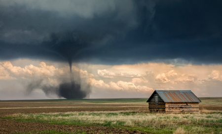 Landspout-tornado hybrid on plains, barn in foreground, Cope, Eastern Colorado, US