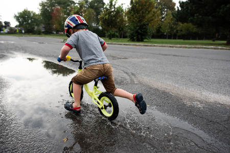 Boy riding bicycle on wet road LANG_EVOIMAGES