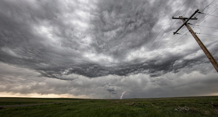 Wave-like asperatus undulatus clouds show gravity waves, a cloud-to-ground lightning strike in the distance, Hillsdale, Wyoming, US LANG_EVOIMAGES