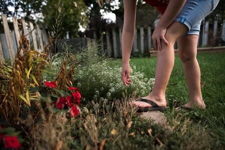 Girl reaching out for flower in garden