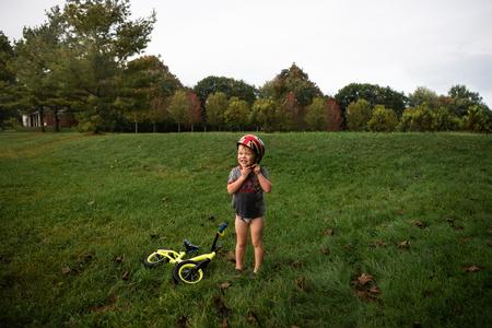 Boy fastening helmet in park