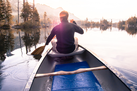 Young man canoeing on Echo Lake, rear view, High Sierras, California, USA LANG_EVOIMAGES
