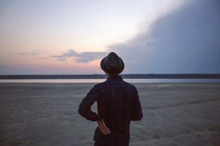 Man in hat on beach at sunset, Odessa, Ukraine LANG_EVOIMAGES