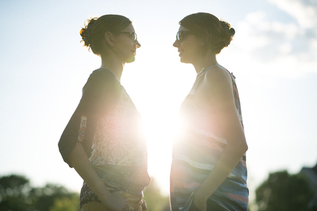 Twin sisters in park at sunset