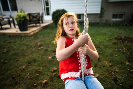 Girl swinging on rope in garden LANG_EVOIMAGES