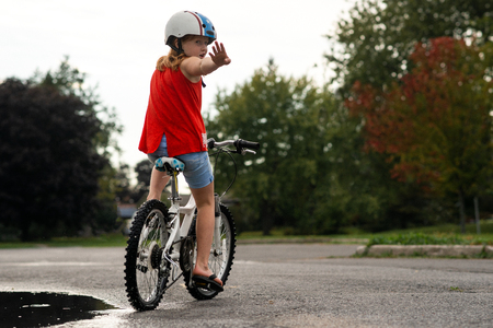 Girl on bicycle stopping in middle of road