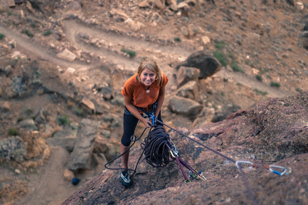 Woman holding climbing rope looking up smiling, Smith Rock State Park, Terrebonne, Oregon, United States