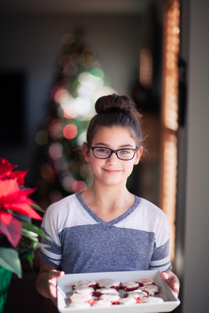 Girl holding tray of homemade christmas cookies in living room,portrait LANG_EVOIMAGES