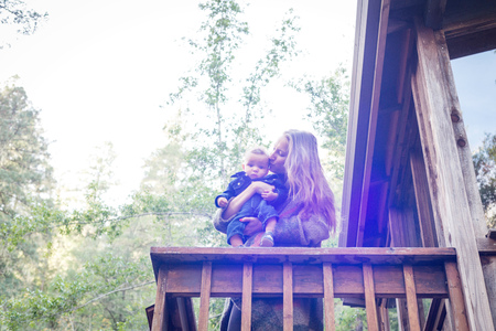 Mother with baby son on balcony of wooden house in forest,Cazadero,California,USA LANG_EVOIMAGES