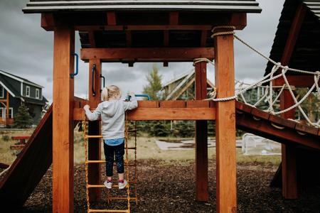 Girl climbing ladder to playground platform,rear view