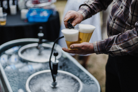 Man pouring beer from keg in cooling bath at barbecue,cropped LANG_EVOIMAGES