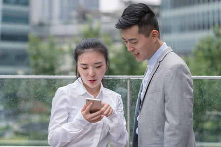 Young businesswoman and man looking at smartphone in city,Shanghai,China LANG_EVOIMAGES