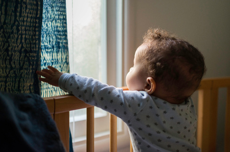 Baby boy standing up in crib looking out through window