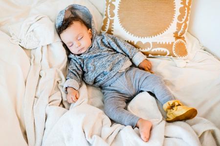 Baby boy wearing hoody asleep on blanket