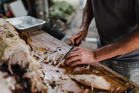 Man slicing hog roast on table,cropped