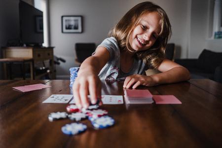 Girl playing cards at table,placing gambling chips